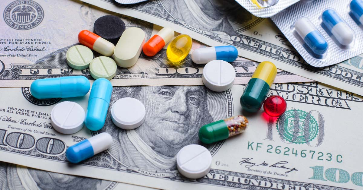 Different colorful pills capsules on money bills. Concept of expensive treatment, medicine, medical insurance.